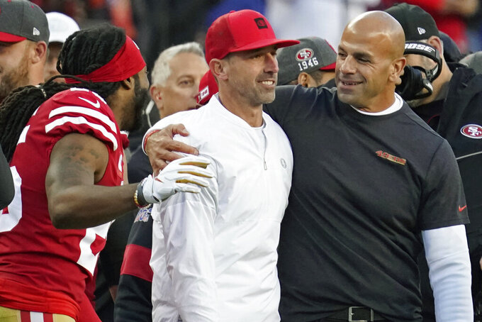 San Francisco 49ers head coach Kyle Shanahan, center, is greeted by with cornerback Richard Sherman, left, and defensive coordinator Robert Saleh, right, in the final minutes of the second half of an NFL divisional playoff football game against the Minnesota Vikings, Saturday, Jan. 11, 2020, in Santa Clara, Calif. The 49ers won 27-10. (AP Photo/Tony Avelar)