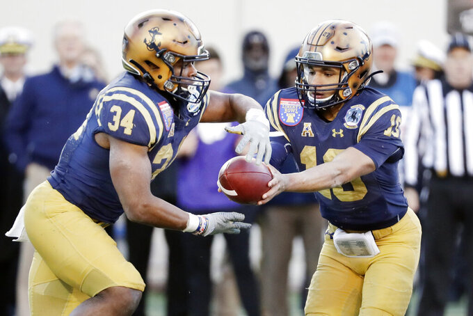 Navy quarterback Malcolm Perry (10) hands off to fullback Jamale Carothers (34) in the first half of the Liberty Bowl NCAA college football game against Kansas State Tuesday, Dec. 31, 2019, in Memphis, Tenn. (AP Photo/Mark Humphrey)