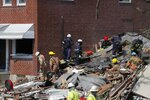 Authorities walk among the piles of debris from an explosion in Baltimore on Monday, Aug. 10, 2020. The