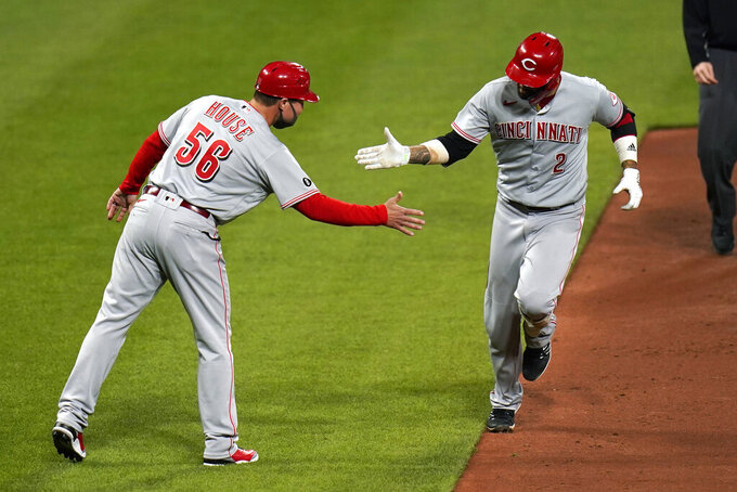 Cincinnati Reds' Nick Castellanos (2) is congratulated by third base coach J.R. House after hitting a solo home run during the sixth inning of a baseball game against the St. Louis Cardinals Friday, April 23, 2021, in St. Louis. (AP Photo/Jeff Roberson)