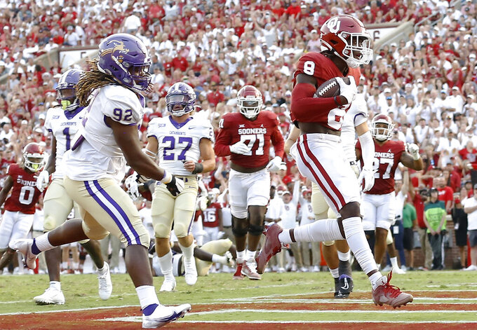Oklahoma wide receiver Michael Woods II (8) scores a touchdown ahead of Western Carolina defensive end Darrius Bell (92) during the first half of an NCAA college football game Saturday, Sept. 11, 2021, in Norman, Okla. (AP Photo/Alonzo Adams)