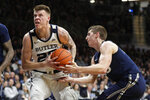 Xavier forward Jason Carter (25) tries to strip the ball from Butler forward Sean McDermott (22) in the first half of an NCAA college basketball game in Indianapolis, Wednesday, Feb. 12, 2020. (AP Photo/Michael Conroy)