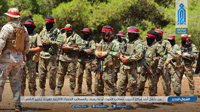 FILE - This Aug 20, 2018 photo, provided by the al-Qaida-affiliated Ibaa News Network, shows fighters of the al-Qaida-linked coalition known as Hay'at Tahrir al-Sham, training in Idlib province, Syria. After eight months of relative calm, Idlib is once again a theater for bloody military operations as Syrian government troops, backed by Russia, push their way into the rebel-held enclave in a widening offensive. The violence in May 2019 threatens to completely unravel a crumbling cease-fire agreement reached between Turkey and Russia last September. (Ibaa News Network, via AP, File)