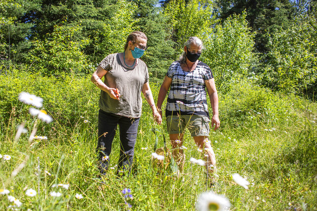 Heather Roan Robbins, left, and Wren Walker Robbins look for invasive plants during a walk around their property near Ronan, Mont., on July 11, 2020. The two have been attempting the walks to search for weeds since their recovery from COVID-19, but say they still find themselves out of breath on their walks four months after having the sickness. (Sara Diggins/The Missoulian via AP)