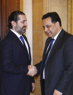 In this photo released by Lebanon's official government photographer Dalati Nohra, Lebanese Prime Minister-designate Hassan Diab, right, shakes hands with outgoing Prime Minister Saad Hariri, left, in Beirut, Lebanon, Friday, Dec. 20, 2019. Diab, a professor at the American University of Beirut, was named by President Michel Aoun after a day of consultations with lawmakers in which he gained a simple majority in the 128-member parliament. He won support from 69 lawmakers, including the parliamentary bloc of the Shiite Hezbollah and Amal movements, as well as lawmakers affiliated with Aoun. (Dalati Nohra via AP)
