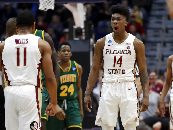 Florida State's Terance Mann (14) celebrates with David Nichols (11) as Vermont's Ben Shungu (24) looks on during the second half of a first round men's college basketball game in the NCAA Tournament, Thursday, March 21, 2019, in Hartford, Conn. (AP Photo/Elise Amendola)