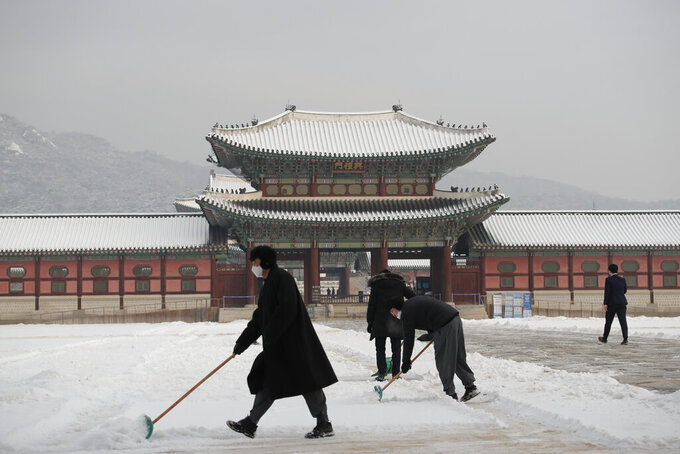 People wearing face masks as a precaution against the coronavirus clear snow at the Gyeongbok Palace, one of South Korea's well-known landmarks, in Seoul, South Korea, Wednesday, Jan. 13, 2021. (AP Photo/Lee Jin-man)