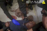 In this Feb. 12, 2019 image made from video and released by the Forsyth County, (N.C). Jail, authorities restrain John Neville in his cell as a nurse speaks with him, in Winston-Salem, N.C. The body-cam video from the jail shows Neville struggling with jail guards to get up from the floor where he was lying on his back, shouting that he couldn't breathe and calling out