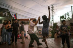 In this May 11, 2019 photo, Irene Vaamondez, right, dances with a neighbor as musicians play live music at a public plaza where neighbors socialize in Caracas, Venezuela, at sunset. (AP Photo/Rodrigo Abd)