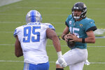 Jacksonville Jaguars quarterback Gardner Minshew II (15) looks for a receiver over Detroit Lions defensive end Romeo Okwara (95) during the second half of an NFL football game, Sunday, Oct. 18, 2020, in Jacksonville, Fla. (AP Photo/Phelan M. Ebenhack)