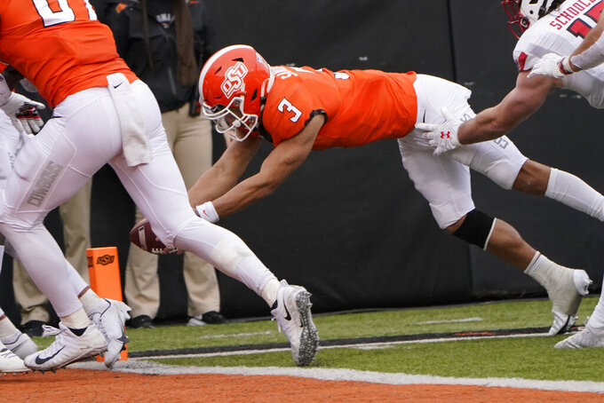 Oklahoma State quarterback Spencer Sanders (3) dives into the end zone for a touchdown in the second half of an NCAA college football game against Texas Tech in Stillwater, Okla., Saturday, Nov. 28, 2020. (AP Photo/Sue Ogrocki)