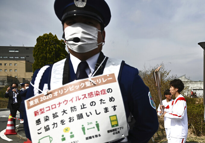 A guard with a sign for coronavirus precautions stands as Japanese Azusa Iwashimizu, right, a member of Japan women's national football team, carries an Olympic Torch during the torch relay grand start outside J-Village National Training Center in Naraha, Fukushima prefecture, northeastern Japan, Thursday, March 25, 2021. The torch relay for the postponed Tokyo Olympics began its 121-day journey across Japan on Thursday and is headed toward the opening ceremony in Tokyo on July 23. (Philip Fong/Pool Photo via AP)