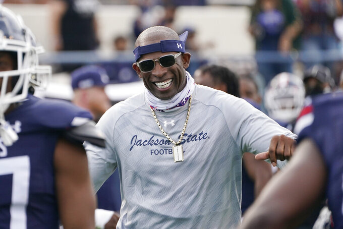 Jackson State football coach Deion Sanders smiles as he greets his defensive squad after they had recovered a Mississippi Valley State fumble for a touchdown during the second half of an NCAA college football game, Sunday, March 14, 2021, in Jackson, Miss. (AP Photo/Rogelio V. Solis)
