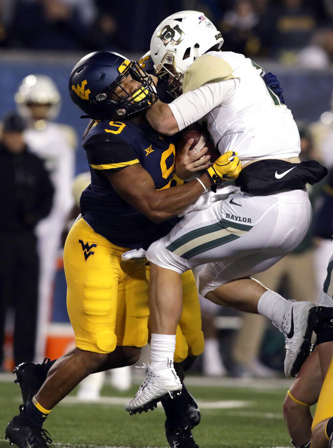 West Virginia safety Jovanni Stewart (9) sacks Baylor quarterback Charlie Brewer, right, during the first half of an NCAA college football game Thursday, Oct. 25, 2018, in Morgantown, W.Va. (AP Photo/Raymond Thompson)