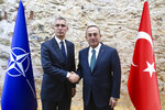 FILE - In this file photo dated Friday, Oct. 11, 2019, Turkish Foreign Minister Mevlut Cavusoglu, right, shakes hands with NATO Secretary General Jens Stoltenberg in Istanbul.  The festering dispute between France and Turkey over a naval standoff in the Mediterranean Sea has shone a glaring searchlight on NATO's struggle to keep order among its ranks, especially when its allies are perceived to be on different sides of a conflict like in Libya. (Turkish Foreign Ministry file via AP)