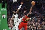 Atlanta Hawks forward Cam Reddish (22) shoots against Boston Celtics guard Jaylen Brown (7) during the first quarter of an NBA basketball game Friday, Jan. 3, 2020, in Boston. (AP Photo/Elise Amendola)