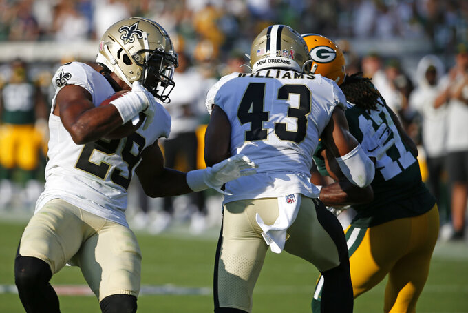New Orleans Saints cornerback Paulson Adebo, left, intercepts a pass thrown by Green Bay Packers quarterback Aaron Rodgers during the second half of an NFL football game, Sunday, Sept. 12, 2021, in Jacksonville, Fla. (AP Photo/Stephen B. Morton)