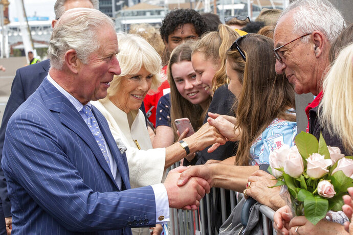 Britain's Prince Charles, left, and his wife Camilla, second left, greet members of the public during a walk at Viaduct Harbour in Auckland during their royal visit to New Zealand, Tuesday, Nov. 19, 2019. The visit is part of a week-long tour of the country which also takes in Christchurch and Kaikoura. (David Rowland/Pool Photo via AP)
