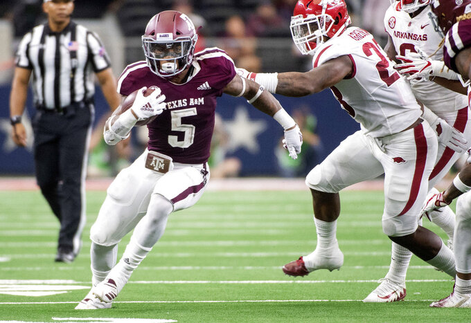 Texas A&M running back Trayveon Williams (5) turns upfield past Arkansas linebacker Dre Greenlaw (23) during the second quarter of an NCAA college football game Saturday, Sept. 29, 2018, in Arlington, Texas. (AP Photo/Jeffrey McWhorter)