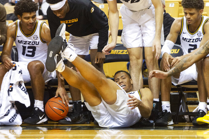 Missouri's Javon Pickett, center, tries to save a ball from going into the Missouri bench during the first half of an NCAA college basketball game against Charleston Southern Tuesday, Dec. 3, 2019, in Columbia, Mo. (AP Photo/L.G. Patterson)