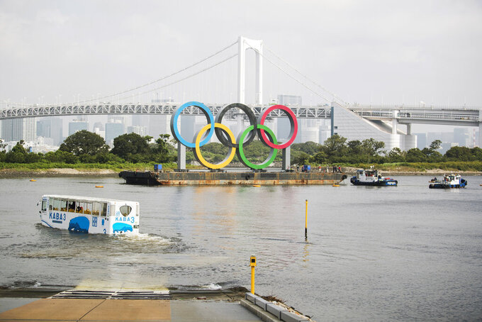 """An amphibious bus wades through water for a test cruise as workers on tugboats prepare to move a symbol installed for the Olympic and Paralympic Games Tokyo 2020 on a barge away from its usual spot off the Odaiba Marine Park in Tokyo Thursday, Aug. 6, 2020. The five Olympic rings floating on a barge in Tokyo Bay were removed on Thursday for what is being called """"maintenance,"""" and officials says they will return to greet next year's Games. The Tokyo Olympics have been postponed for a year because of the coronavirus pandemic and are to open on July 23, 2021. The Paralympics follow on Aug. 24. (AP Photo/Hiro Komae)"""