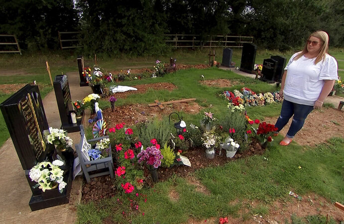 In this image made from video taken on Tuesday, Sept. 10, 2019, Nicola Bowler stands in front of the grave of her father, Derek Wood, in Birmingham, England. Bowler released a helium balloon into the sky to commemorate the one-year anniversary of her father's death. It ended up traveling more than 1,000 miles (1,700 kilometers) across land and sea and was found by a farmer in Poland. (AP Photo)