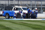 Workers make repairs part of the track during the NASCAR Series auto race at Indianapolis Motor Speedway, Sunday, Aug. 15, 2021, in Indianapolis. (AP Photo/Rob Baker)