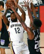 New Orleans Pelicans' Sindarius Thornwell (12) drives the ball against Sacramento Kings' Harry Giles III (20) during the first half of an NBA basketball game Tuesday, Aug. 11, 2020, in Lake Buena Vista, Fla. (Mike Ehrmann/Pool Photo via AP)