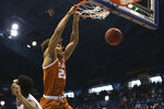 Texas senior forward Jericho Sims dunks over Kansas defense in the first half of an NCAA college basketball game  Saturday, Jan. 2, 2021, in Lawrence, Kan. (Evert Nelson//The Topeka Capital-Journal via AP)