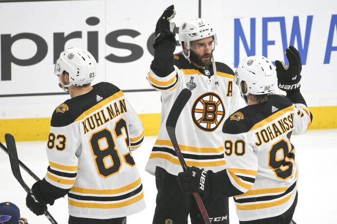 Boston Bruins center Patrice Bergeron (37) celebrates with Marcus Johansson (90), of Sweden, and Karson Kuhlman (83) after the Bruins beat the St. Louis Blues in Game 6 of the NHL hockey Stanley Cup Final Sunday, June 9, 2019, in St. Louis. The Bruins won 5-1 to even the series 3-3. (AP Photo/Scott Kane)
