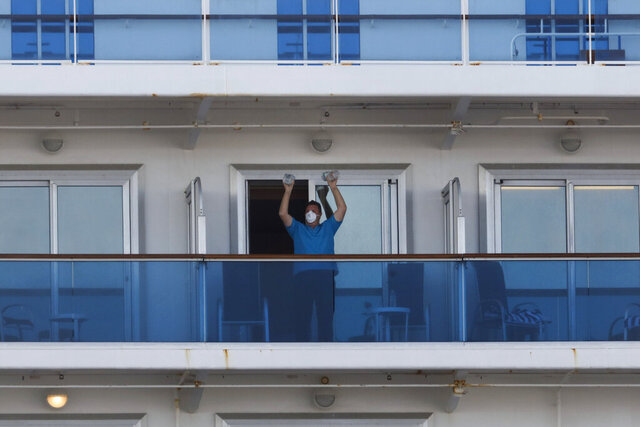 A passenger exercises using two water bottles on the quarantined Diamond Princess cruise ship Wednesday, Feb. 19, 2020, in Yokohama, near Tokyo. Passengers tested negative for COVID-19 will start disembarking Wednesday. (AP Photo/Jae C. Hong)