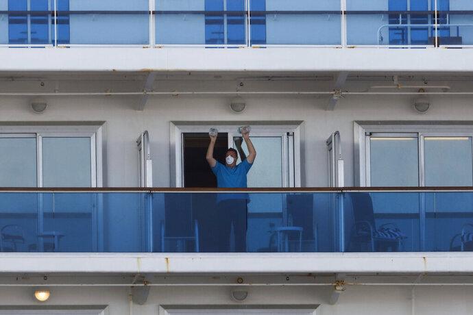 A passenger exercises using two water bottles on the quarantined Diamond Princess cruise ship Wednesday, Feb. 19, 2020, in Yokohama, near Tokyo. Passengers tested negative for COVID-19 will start disembarking Wednesday. (AP Photo/Jae C. Hong)