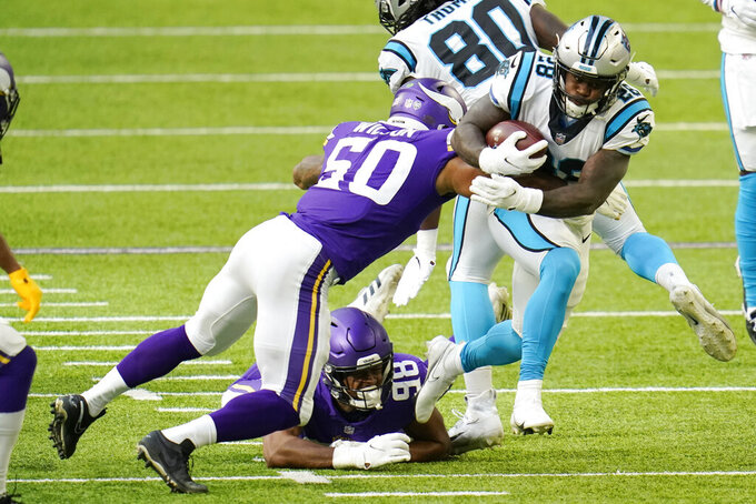 Carolina Panthers running back Mike Davis (28) runs from Minnesota Vikings defenders Eric Wilson (50) and D.J. Wonnum (98) during the first half of an NFL football game, Sunday, Nov. 29, 2020, in Minneapolis. (AP Photo/Jim Mone)