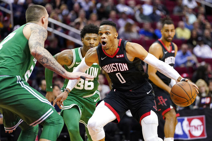Houston Rockets' Russell Westbrook (0) drives toward the basket as Boston Celtics' Daniel Theis, left, defends during the first half of an NBA basketball game Tuesday, Feb. 11, 2020, in Houston. (AP Photo/David J. Phillip)