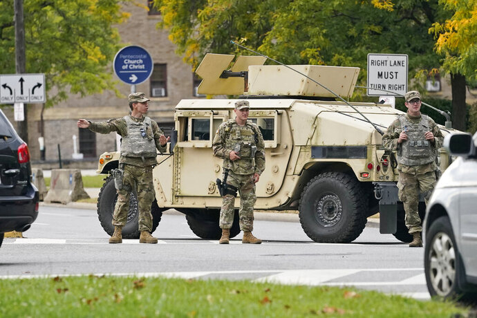 FILE – In this Tuesday, Sept. 29, 2020 file photo, the Ohio National Guard directs traffic away from the debate hall in Cleveland where the first presidential debate between Republican candidate President Donald Trump and Democratic candidate and former Vice President Joe Biden was being held. Ohio Gov. Mike DeWine announced on Tuesday, Jan. 12, 2021 that he has activated 580 National Guard men and women in preparations for potentially armed protests at the U.S. Capitol and the Ohio Statehouse in Columbus, Ohio. (AP Photo/Tony Dejak, File)