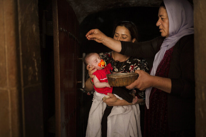In this Aug. 23, 2019 photo, a baby girl is annointed with water from an ancient spring by a Yazidi holy woman at the the Lalish temple near Sheikhan, Iraq. The ancient sect is rebuilding, nearly six years after Islamic State militants launched its coordinated attack on the heartland of the Yazidi community at the foot of Sinjar Mountain in August 2014. (AP Photo/Maya Alleruzzo)
