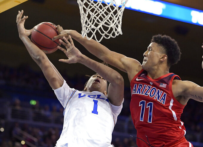 Arizona forward Ira Lee, right, blocks the shot of UCLA center Moses Brown during the second half of an NCAA college basketball game Saturday, Jan. 26, 2019, in Los Angeles. UCLA won 90-69. (AP Photo/Mark J. Terrill)