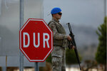 A Turkish soldier stands next to a sign that reads