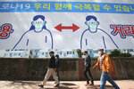 "People wearing face masks pass by a banner displaying precautions against the coronavirus on a street in Seoul, South Korea, Monday, April 5, 2021. The banner reads "" We can overcome Corona 19."" (AP Photo/Ahn Young-joon)"