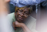 Shirley Newbill listens as guests talk about her son during a vigil for Eric Logan Monday, June 17, 2019 on Washington Street in South Bend, Ind.  Logan, 54, was killed in South Bend early Sunday after someone called police to report a suspicious person going through cars, according to the St. Joseph County prosecutor's office. (Michael Caterina/South Bend Tribune via AP)