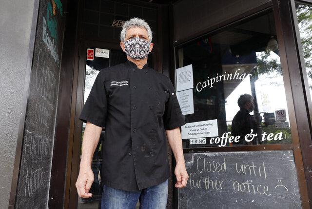 Owner Claudio Gianello stands in the doorway of his temporarily closed Café Beaudelaire restaurant, Tuesday, June 23, 2020, in Ames, Iowa. Within a few weeks of Gov. Kim Reynolds opening bars and restaurants to customers again two major college cities in Iowa are seeing spikes in coronavirus cases among young adults between 19 and 25, reflecting similar trends seen in other states including Florida and Texas. In Ames the surge is serious enough to prompt several owners of restaurants and bars near the Iowa State University campus to close voluntarily just weeks after reopening. (AP Photo/Charlie Neibergall)