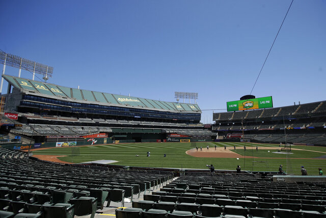 The grounds crew works on the field at Oakland Coliseum before an Oakland Athletics baseball practice in Oakland, Calif., Saturday, July 4, 2020. (AP Photo/Jeff Chiu)