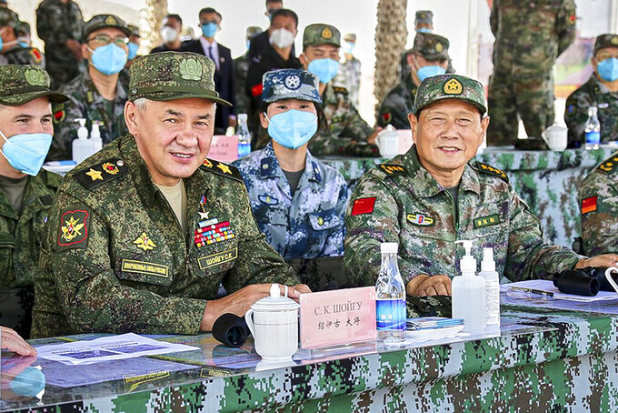 In this handout photo released by Russian Defense Ministry Press Service, Russian Defense Minister Sergei Shoigu and Chinese Defense Minister Wei Fenghe watch a joint military exercise by Russia and China held in the Ningxia Hui Autonomous Region in northwestern China on Friday, Aug. 13, 2021. Shoigu hailed joint war games with China this week as a sign of increasingly close ties and vowed to further expand military cooperation between the two countries. (Savitskiy Vadim/Russian Defense Ministry Press Service via AP)