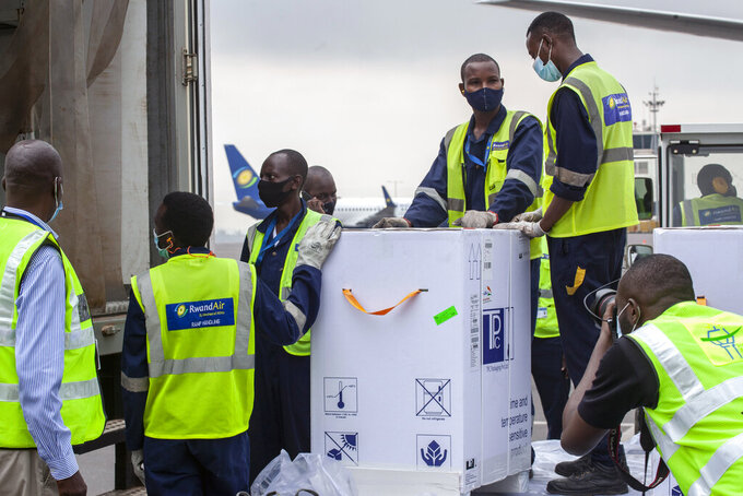 AstraZeneca COVID-19 vaccines are received by airport workers at the airport in Kigali, Rwanda Wednesday, March 3, 2021. More African countries received the long-awaited first deliveries of COVID-19 vaccines on Wednesday, with Kenya, Rwanda, Senegal and Lesotho benefiting from the global COVAX initiative that aims to ensure doses for the world's low-and middle-income nations. (AP Photo/Muhizi Olivier)