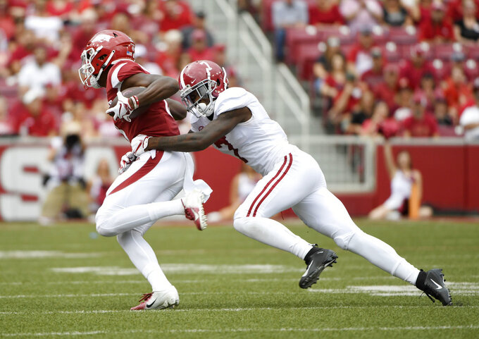 Arkansas receiver Michael Woods is tackled by Alabama defender Trevon Diggs in the first half of an NCAA college football game Saturday, Oct. 6, 2018, in Fayetteville, Ark. (AP Photo/Michael Woods)