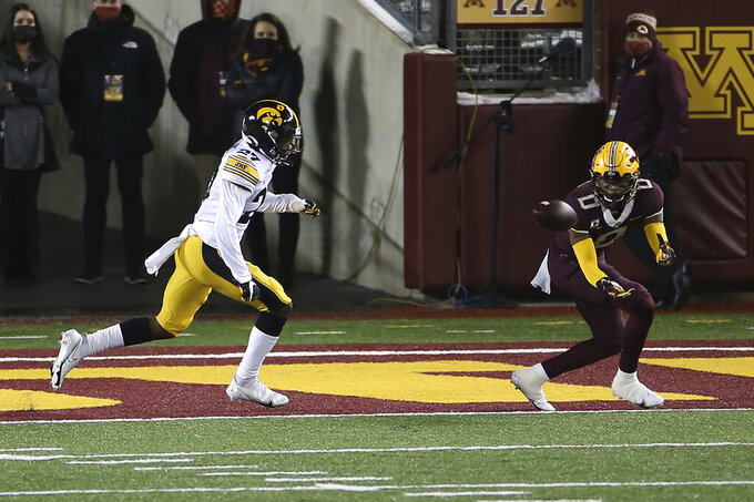 Minnesota wide receiver Rashod Bateman (0) catches a pass for a touchdown, next to Iowa defensive back Jermari Harris (27) during the second half of an NCAA college football game Friday, Nov. 13, 2020, in Minneapolis. Iowa won 35-7. (AP Photo/Stacy Bengs)