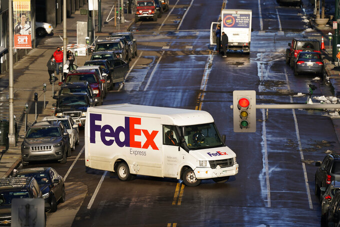 FILE - In this Tuesday, Dec. 29, 2020, file photo, a FedEx delivery vehicle makes a U-turn near the Denver Pavilions, in downtown Denver. FedEx says its profit nearly tripled in its most recent quarter, despite winter weather that hobbled some of its facilities. Online shopping has surged during the pandemic as more people avoid going inside stores. (AP Photo/David Zalubowski, File)