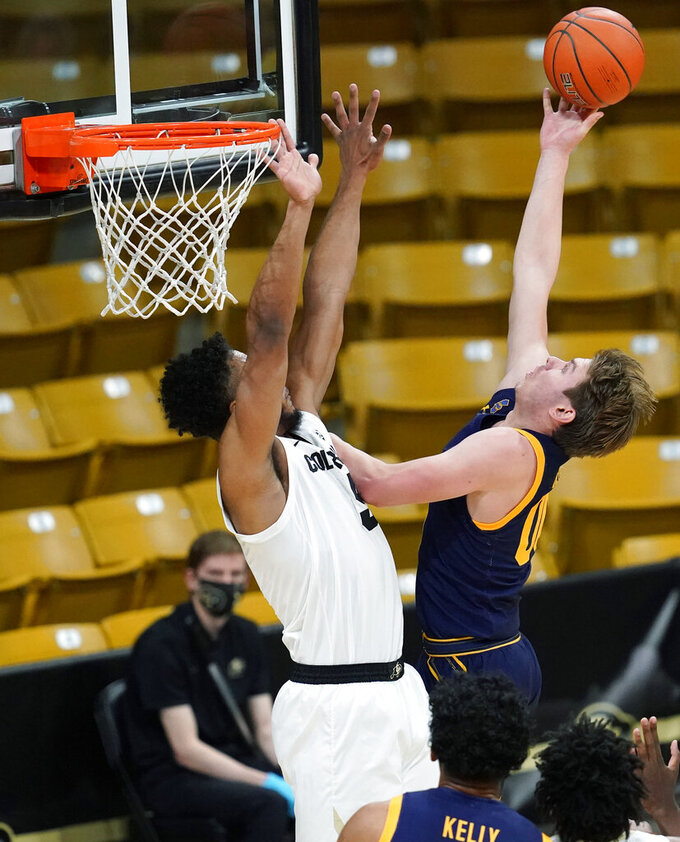 California guard Ryan Betley, right, drives to the rim for a basket as Colorado guard D'Shawn Schwartz defends in the second half of an NCAA college basketball game Thursday, Jan. 14, 2021, in Boulder, Colo. Colorado won 89-60. (AP Photo/David Zalubowski)