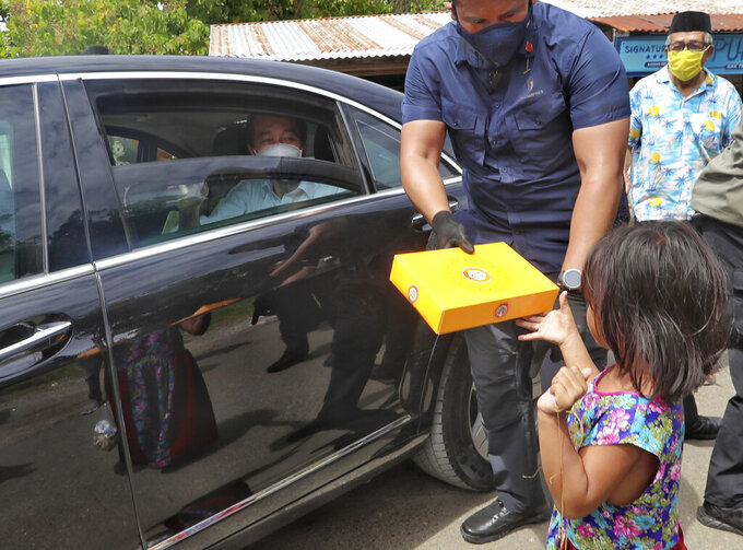 Indonesian President Joko Widodo is helped by his bodyguard to hand out a box of food to a young girl from inside his car during his visit at a quake-hit area in Mamuju, West Sulawesi, Indonesia, Tuesday, Jan. 19, 2021. Widodo visit the areas where a deadly earthquake left thousands of people homeless, to reassure them the government's response is reaching those struggling after the quake. (AP Photo/Josua Marunduh)