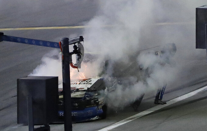 Sheldon Creed runs through smoke after his truck caught fire during a crash in the NASCAR Truck Series auto race Friday, Feb. 15, 2019, at Daytona International Speedway in Daytona Beach, Fla. (AP Photo/Chris O'Meara)